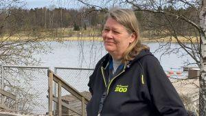 En kvinna i svart jacka med texten Korkeasaari Zoo med ett vattendrag i bakgrunden.