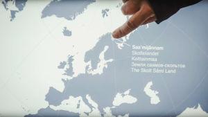 Världskarta, finger pekar på område i nordligaste Norge och Finland.
