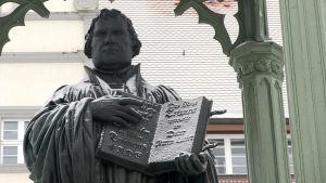Staty som föreställer Martin Luther med Nya testamentet i handen.