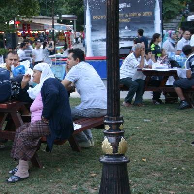 Ihmiset eväineen odottavat iftar-aterian alkua Sultan Ahmedin moskeijan puistossa.