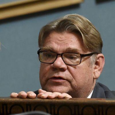 Timo Soini tittar över ett räcke i riksdagen med händerna på räcket.
