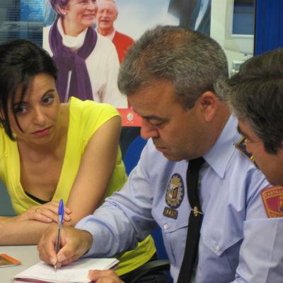 Poliisit ottavat ylös tietoja poliisilaitoksella keltapaitaiselta naiselta.