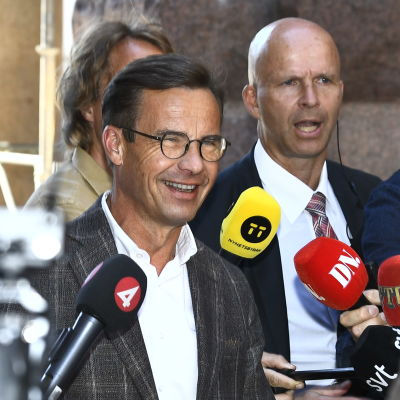 En solbränd och glad Ulf Kristersson möter pressen utanför Sveriges riksdag.