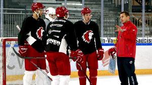 Ville Peltonen diskuterar med spelare på isen.
