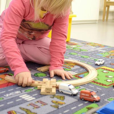 Ett barn leker vid en bilbana.
