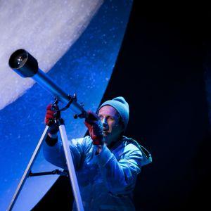 En man i mössa och vantar tittar i en stjärnkikare. I bakgrunden syns en väldig måne.