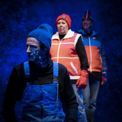En man i vinterkläder ser sig över axeln. Bakom honom står två hotfulla figurer.