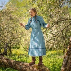 Skådespelaren Stella Laine står uppe i ett somrigt träd.