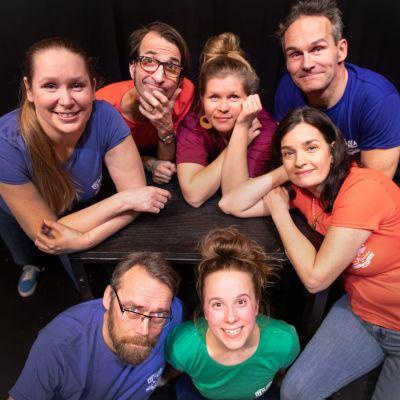 Sju skådespelare i granna t-skjortor mot en svart bakgrund ler upp mot kameran.