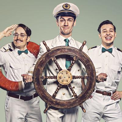 Tre käcka män i sjömansuniformer står på rad bakom ett skeppsroder.