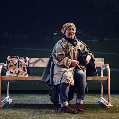 Carola Sarén sitter på en parkbänk tillsammans med hunden Donna.