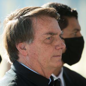 Brasiliens president Jair Bolsonaro utanansiktsmask. Bredvid honom står två män med ansiktsmask