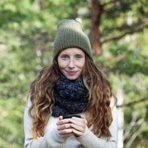 en kvinna står i en skog iklädd skogsvandrigskläder och håller i en kopp