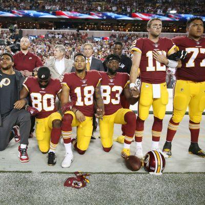NFL-pelaajat polvillaan Yhdysvaltain kansallishymnin aikana.