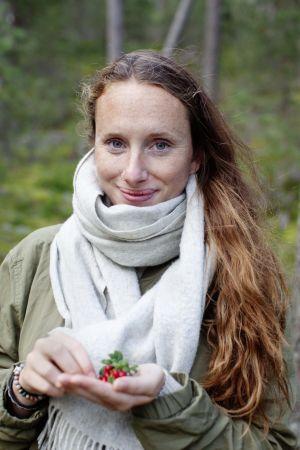 en kvinna står i skogen och håller i några röda bär