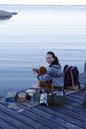 en kvinna sitter på en brygga vid havet och har mat och kärl runtom sig