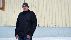 Porträttfoto av man med svart jacka, svart mössa och blå jeans. Han tittar in i kameran. I bakgrunden en träbyggnad som är beigemålad. Snö syns också i bakgrunden.