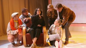 Deltagarna i en skrivargrupp samlas kring ledaren, en dam i svart tröja som sitter i en fåtölj.