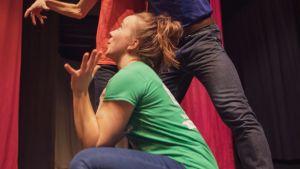En ung kvinnlig skådespelare sitter på huk framför två män som håller fram armarna ovanför henne.