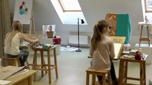 Två barn sitter och målar på en lektion i den kommunala konstskolan i den lettiska staden Valka.