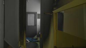 En dörr öppnas till ett mörkt rum, och man ser fötterna av en person som ligger på golvet.