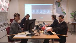 Fyra personer sitter vid varsin dator runt ett bord. Bakom dem syns en stor skärm med olika mindre rutor.