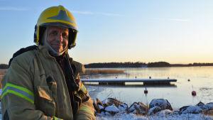 En brandman tittar in i kameran och ler. Bakom honom syns en brygga och fruset vatten. Solen håller på att gå ner.