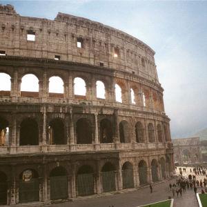 Rooman Colosseumin ylimmät kerrokset sinistä taivasta vasten.