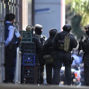 Poliser står utanför ett kafé i Sydney där ett antal människor hålls som gisslan 15.12.2014.