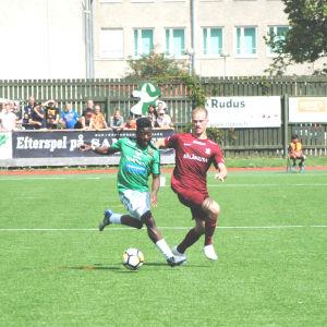 Två fotbollsspelare springer bredvid varandra.