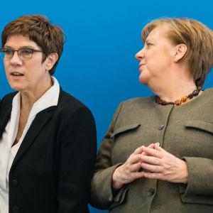 Angela Merkel katsoo Annegret Kramp-Karrenbauerin selän taakse.