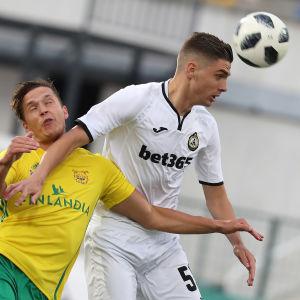 En gulklädd och en vitklädd fotbollspelare i nickduell.