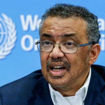 En man i glasögon och kostym sitter bakom ett par mikrofoner med WHO:s logga i bakgrunden.