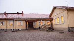 En gul träbyggnad med rött tak. Bilden är tagen ganska nära huset så att man ser huvudingången.
