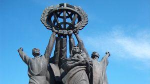 Staty som avbilar personer som tillsammans håller upp jordklotet.