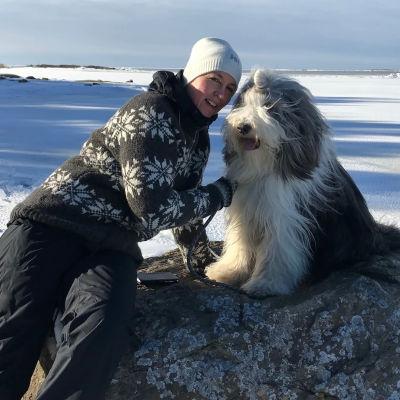 Patrica Strömbäck med sin hund på en sten vid en frusen strand.