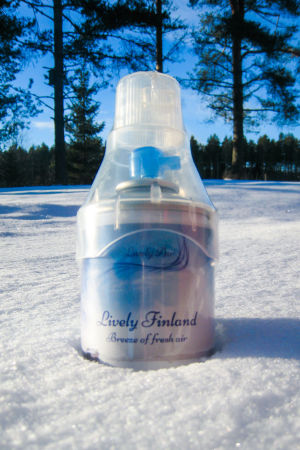 En flaska med frisk luft från Finland nedstucken i snön med träd i bakgrunden