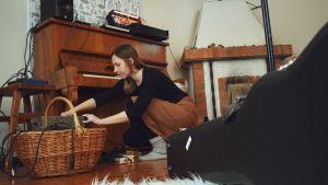 Laura Naukkarinen sitter på huk och plockar i en korg full med sladdar.
