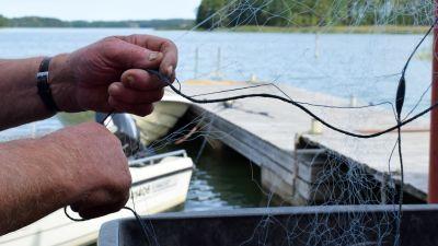 En par gamla händer håller i ett fiskenät, somrigt hav och båtar i bakgrunden.
