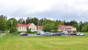Almahemmet i Kimito, grön gräsmatta och bilar på parkeringar framför huset.