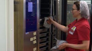 En köksarbetare i röda arbetskläder tar ut mat ur ett värmeskåp.