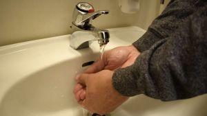 En person tvättar händerna.