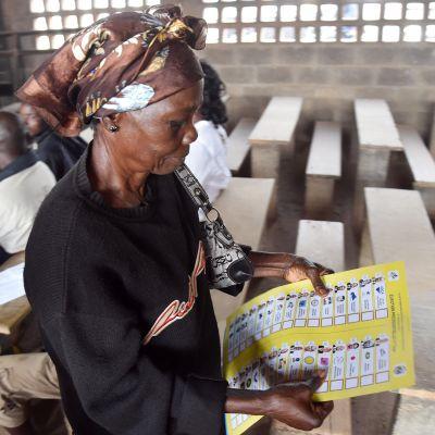 Äänestäjä tarkastelee listaa presdienttiehdokkaista äänestyspaikalla Banguissa 30. joulukuuta.