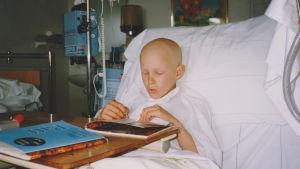 Aron Anderson när han var cancersjuk som barn. Ligger i en sjukhussäng och läser.