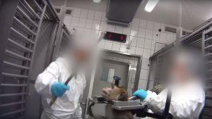 Två laboratoriearbetare står runt en faststpänd apa. Deras ansikten är utsuddade.