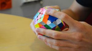 Närbild på två händer som håller i en färggrann pusselkub. Pusslet är egentligen inte format som en kub utan som en dodekaeder.