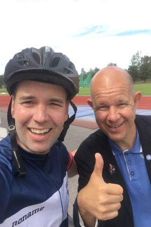 Programledaren Daniel Olin med cyklehjälm på huvudet tillsammans med sportjournalisten Kaj Kunnas på en idrottsplan i Karis.
