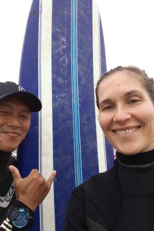 Malin Kivelä, surfinstruktör och bräda. Bägge ler, han visar ett tecken med fingrarna.
