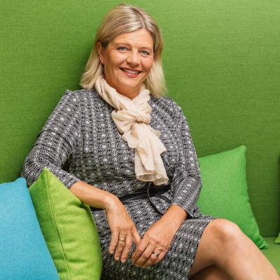 Henkilökuva, Reija Hyvärinen istuu vihreällä sohvalla