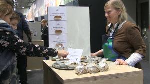 En kvinna säljer finländska knäckebröd på en mässa.